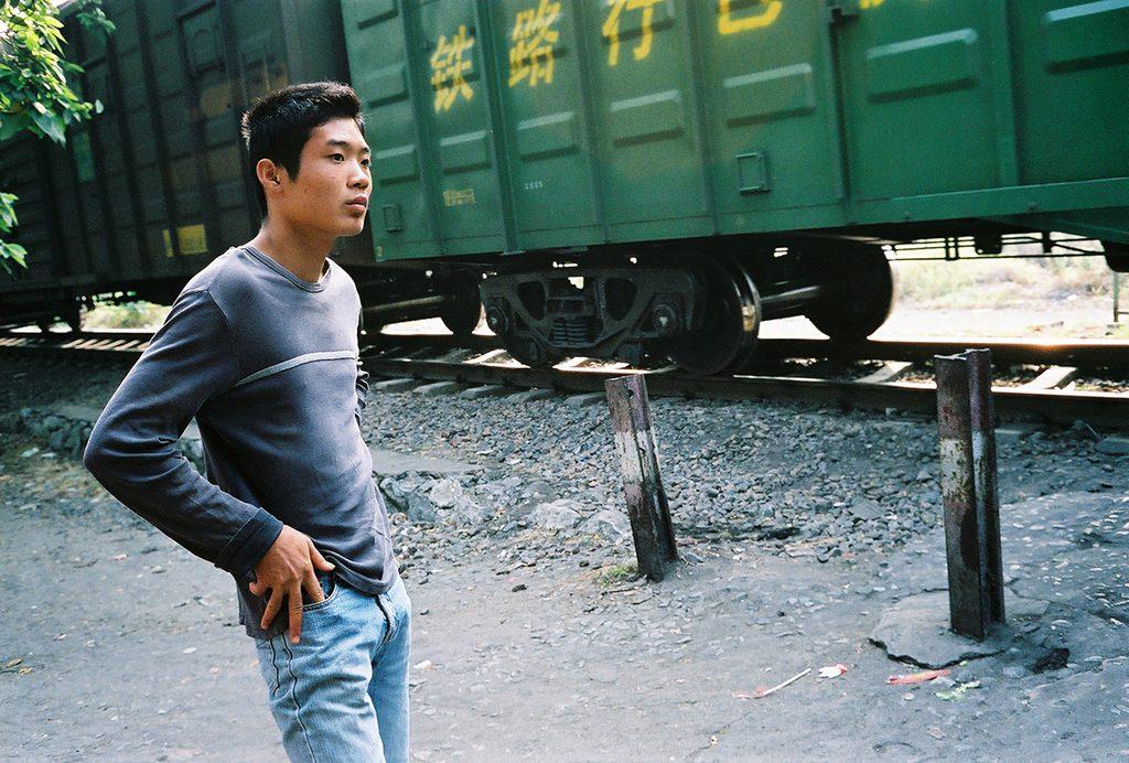 Jeune homme au passage d'un train de marchandises